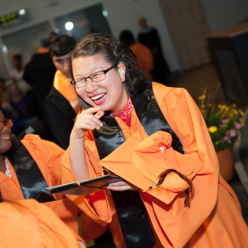 High school student with medium skin tone and dark hair, wearing an orange graduation gown, smiling and chatting with other graduates.
