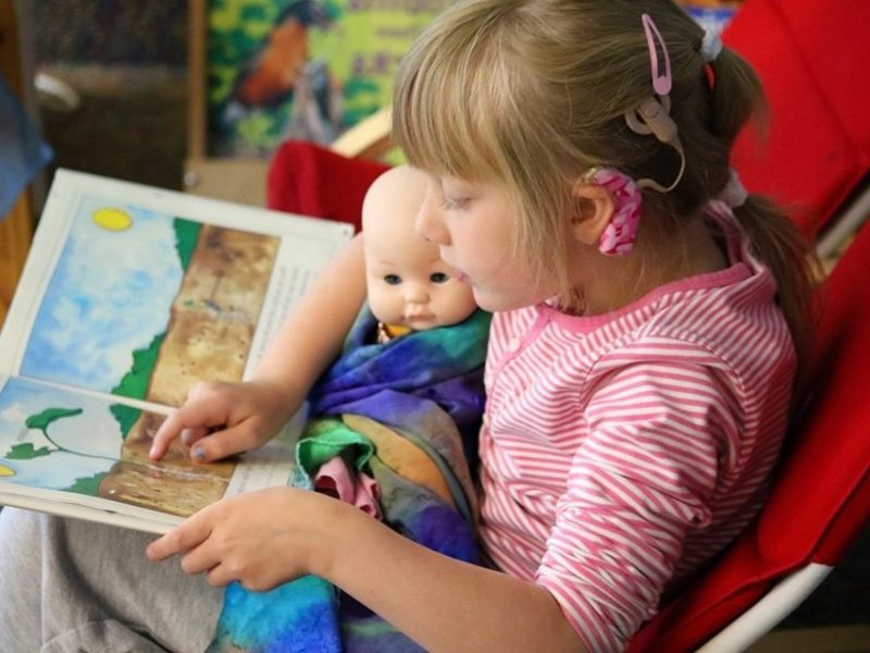 Seven year old girl reading book to doll.