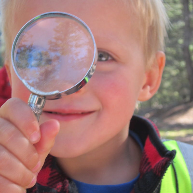 Child with light skin and blond hair is looking through a magnifying glass.
