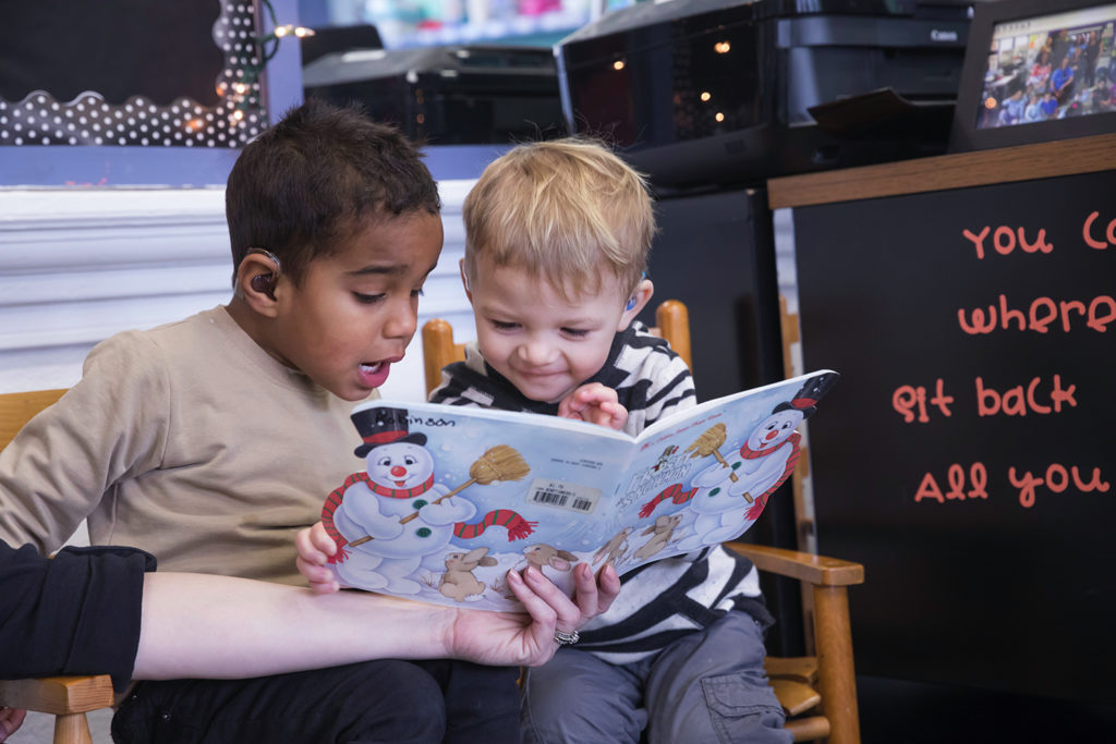 Two five year old boys sitting together reading a book.