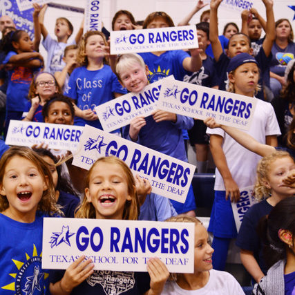 """Students wearing blue tee shirts, holding """"Go Rangers"""" signs."""