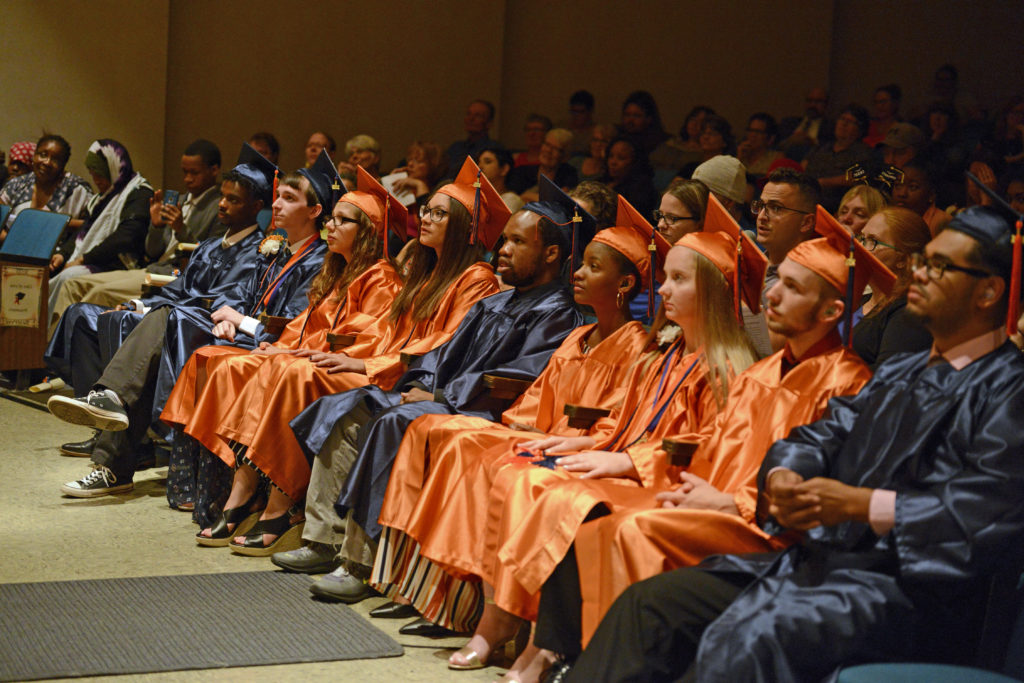 Group of 10 students in either orange or black graduation gowns, seated, with audience behind them.