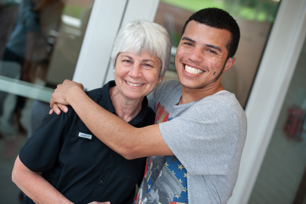 Teenage boy hugging middle aged woman, both smiling.