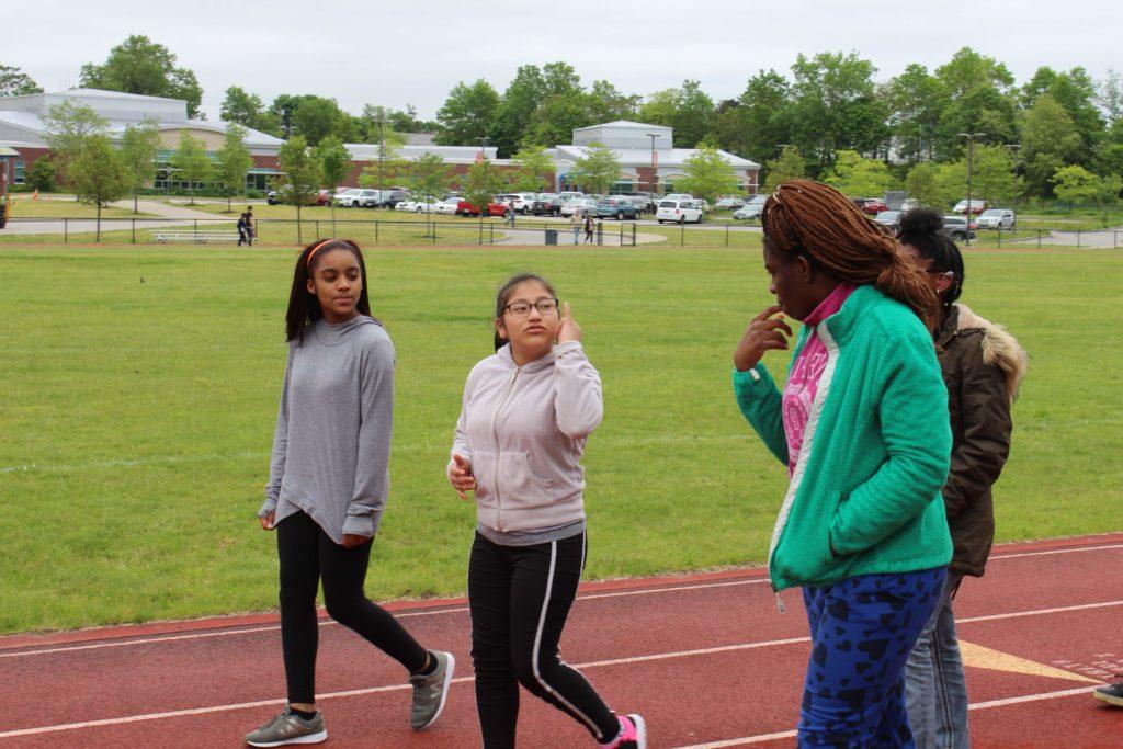 Four high school girls walking on a running track.