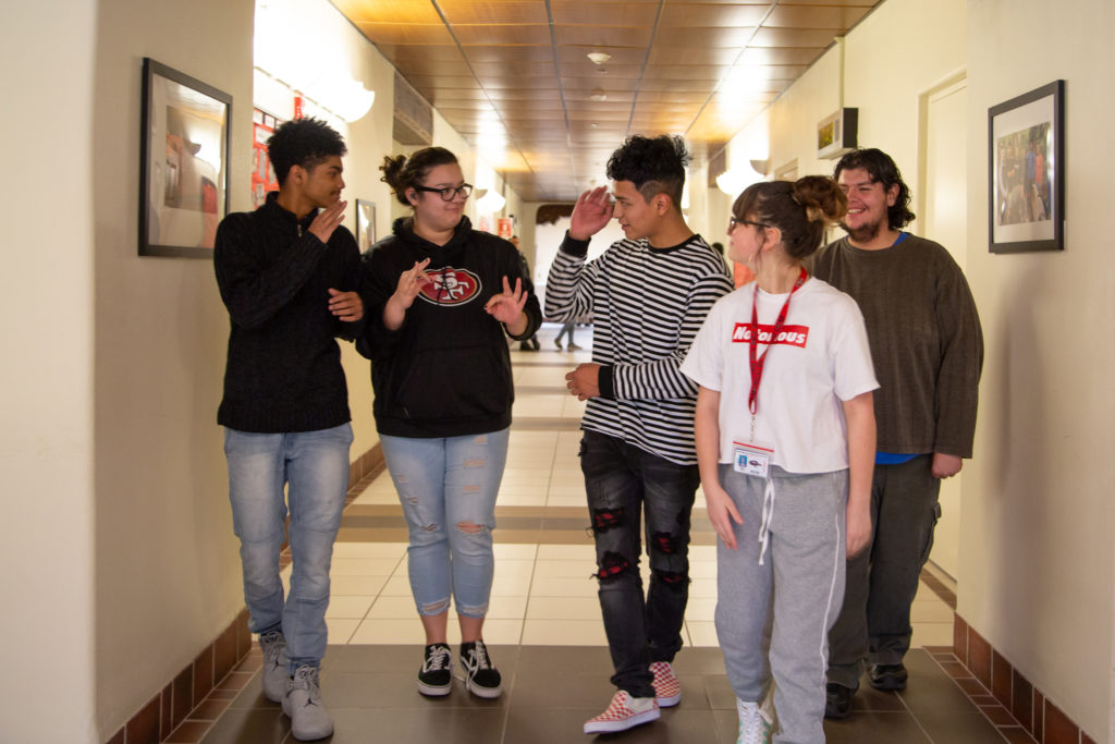 Five high schoolers walking down a school hall.