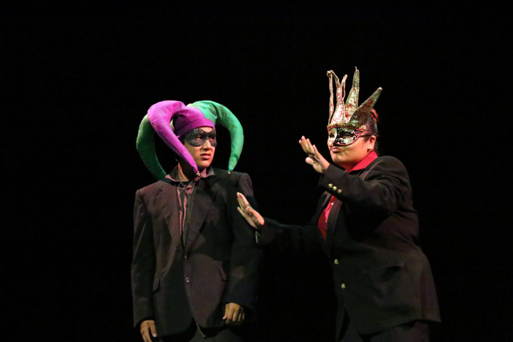 Two high school males in black suits and carnivale masks on dark stage.