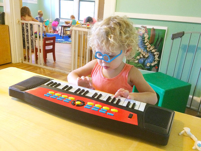 Young blond child with upside down blue glasses playing a desktop organ.