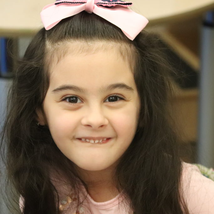 Smiling six year old girl with pink bow in hair.