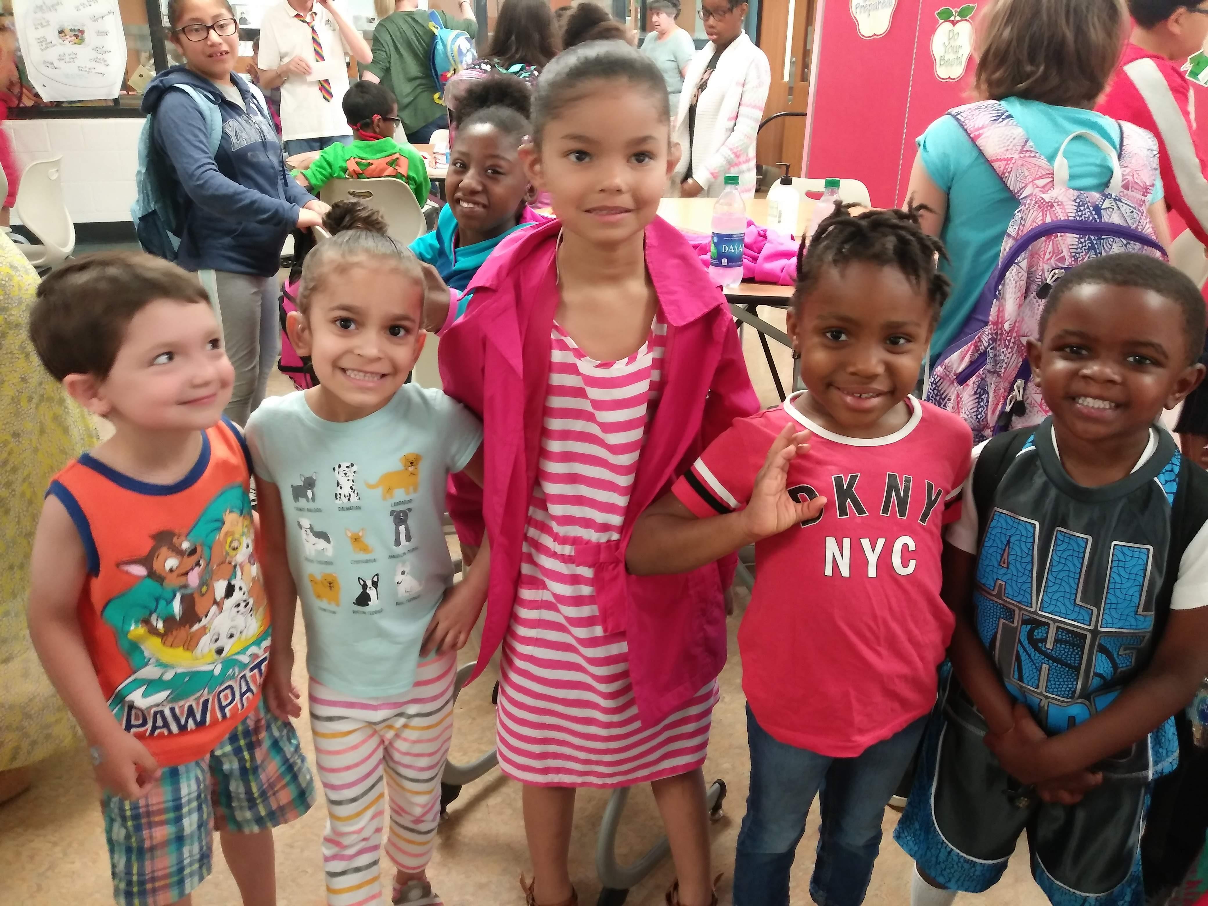Five preschoolers standing together.