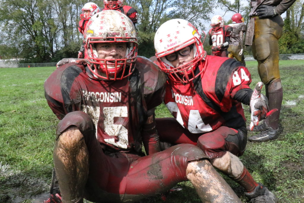 Two muddy football players in red uniforms.