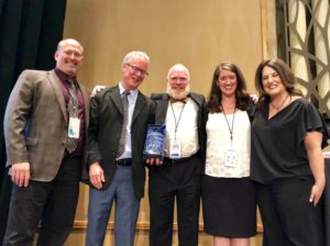 Group of five four adults standing with an award winner.