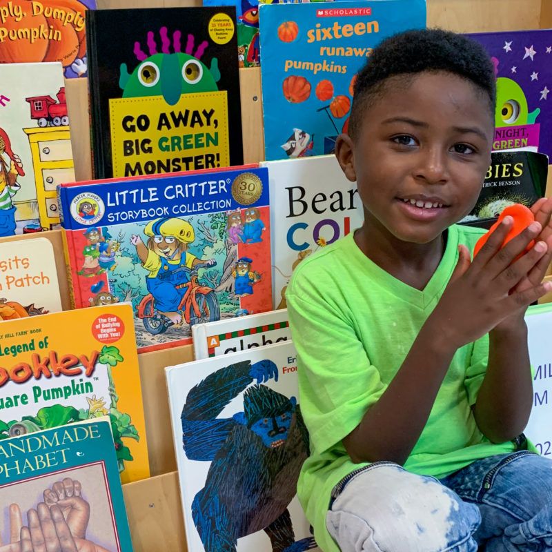 Young boy sitting in front of a display of children's books.