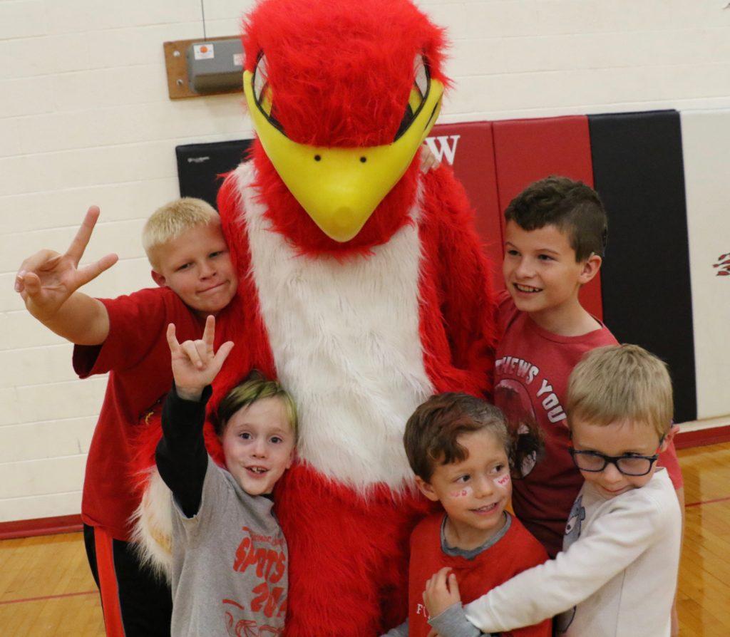 Four young children surrounding firebird mascot.