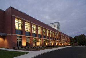 Rectangular brick building with large, lit windows in front of darkening sky.