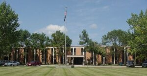 Long brick building with American flag and North Dakota flag flying on one pole in front.